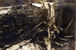Flood 1916 [Close-up of damage to an unknown area.  Loose pieces of wood are piled high next to...