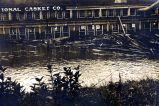 Flood 1916 [Building in background with flood waters in foreground.  Shows loose pieces of...